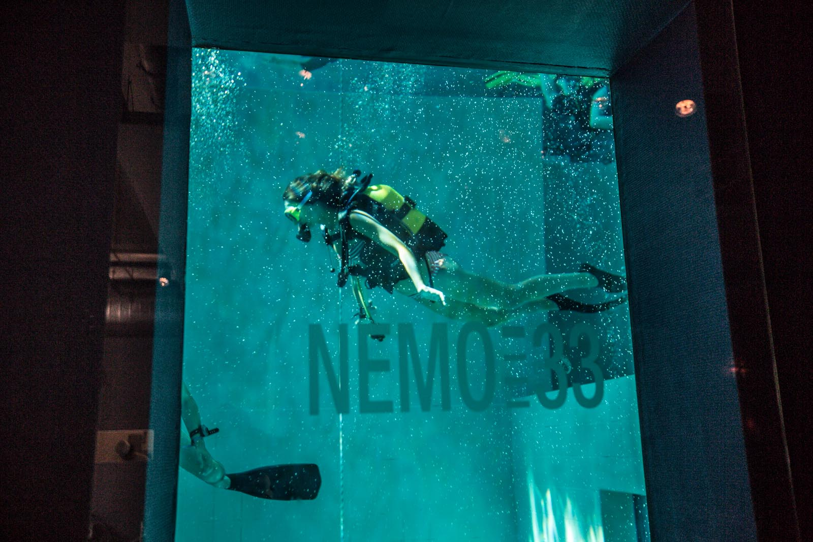 An actual diver seen through the observation window of the restaurant and bar at Nemo 33.